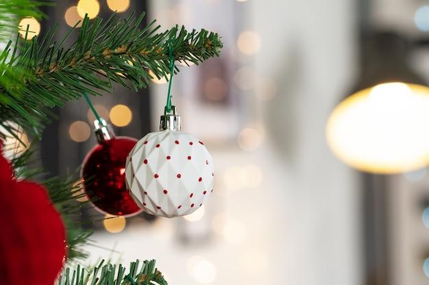 Adornos rojos y blancos colgando de un árbol de navidad de cerca