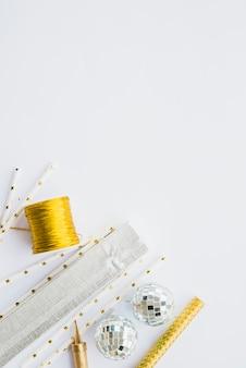 Adornos de varitas junto a bolas y bobina de cinta.