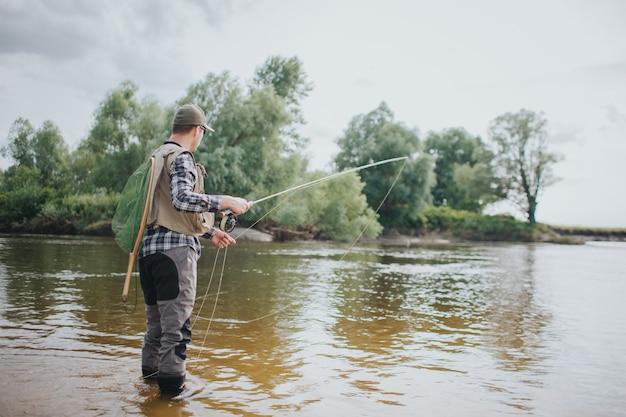 El adulto se para en la caña y sostiene la caña en las manos. él está pescando. guy sostiene la caña en una mano y parte de la cuchara en la otra. también el hombre tiene una red de pesca en la espalda.