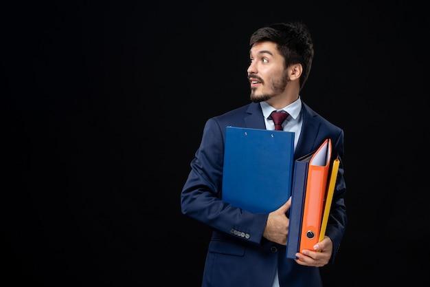 Adulto confundido en traje sosteniendo varios documentos y mirando en algún lugar de la pared oscura aislada