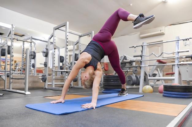 Adulto hermosa mujer rubia haciendo estiramientos practicando yoga en el gimnasio