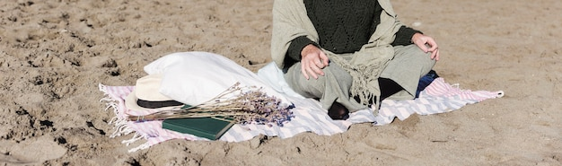 Adulto irreconocible meditando al aire libre