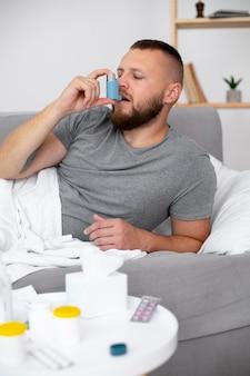 Adulto joven en casa que sufre de enfermedad