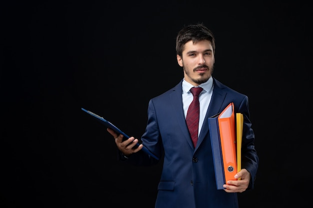 Adulto joven confiado en traje sosteniendo varios documentos en la pared oscura aislada
