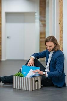 Adulto joven infeliz hombre atractivo con caja de pertenencias personales sentado en el piso de la oficina mirando el contenido