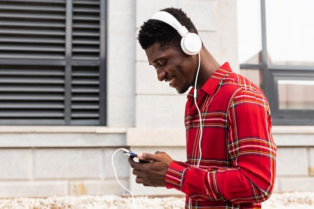 Adulto joven de lado en camisa roja escuchando música