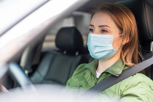 Adulto joven con una máscara de protección y conducir