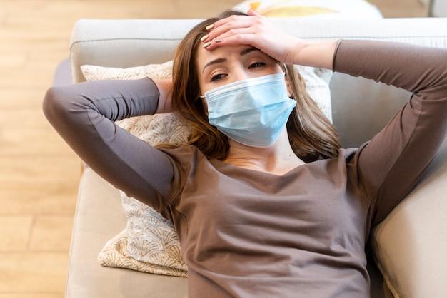 Adulto joven con una máscara de protección en el sofá