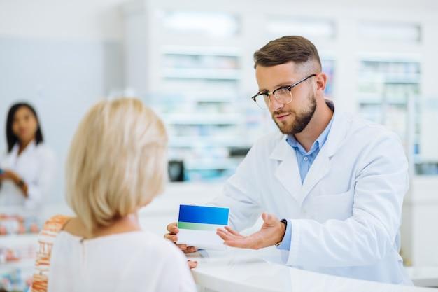 Adulto joven. persona del sexo masculino guapo con uniforme estéril mientras trabajaba en la farmacia