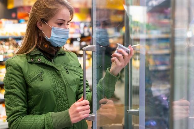Adulto joven usando una máscara de protección y recogiendo productos