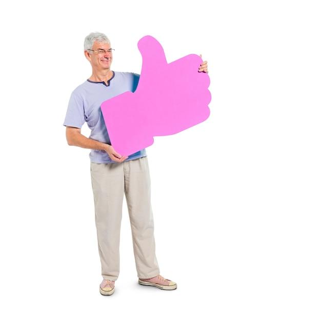 Adulto maduro que sostiene el símbolo de los pulgares arriba