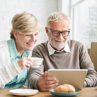 Adulto mayor que usa concepto de la tableta del dispositivo de digitaces
