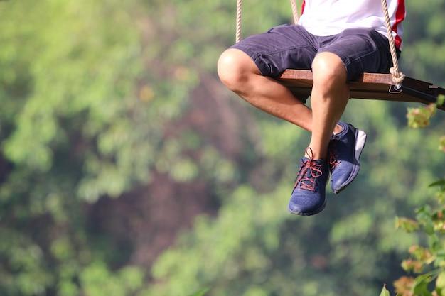 Adulto piernas sentado en el columpio soledad jugando en el parque juguetón y feliz el fondo exterior
