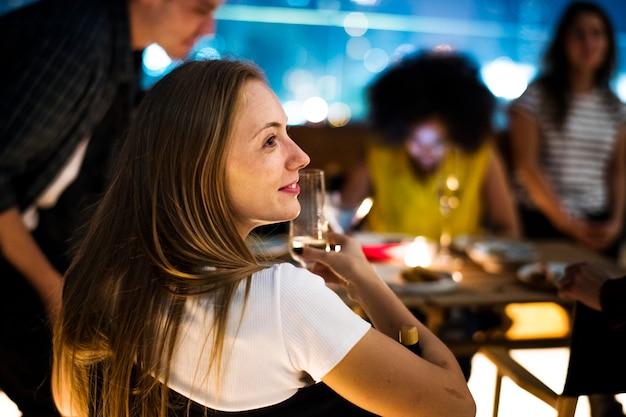Los adultos jóvenes cenan con amigos en un restaurante en la azotea.