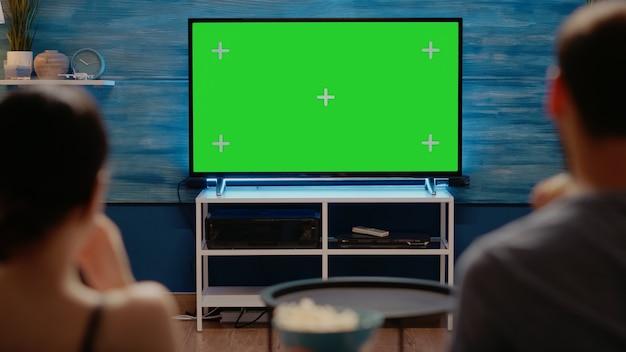 Adultos jóvenes mirando la pantalla verde de tecnología moderna