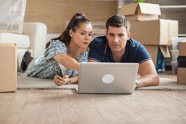 Los adultos jóvenes que usan su computadora portátil en el piso nuevo para muebles nuevos