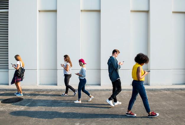 Adultos jóvenes que usan teléfonos inteligentes cuando caminan al aire libre.