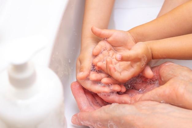 Adultos y niños se lavan las manos. manos en espuma de jabón antibacteriano. protección contra bacterias, coronavirus. higiene de manos. lavarse las manos con agua. muchas manos