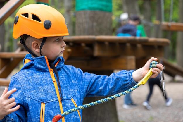 Adventure climbing high wire park: niño en curso con casco de montaña y equipo de seguridad.
