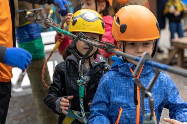 Adventure climbing high wire park: niños en curso con casco de montaña y equipo de seguridad.