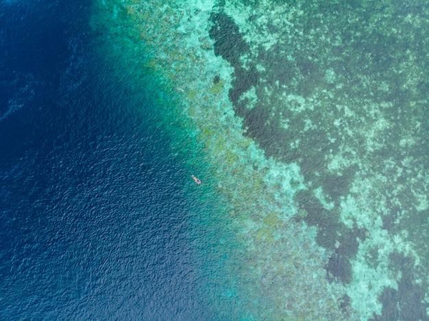 Aéreo de arriba abajo, personas que bucean en el arrecife de coral del mar caribe tropical, agua azul turquesa