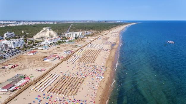 Aéreo. numerosos turistas en la playa de monte gordo. vista desde el cielo