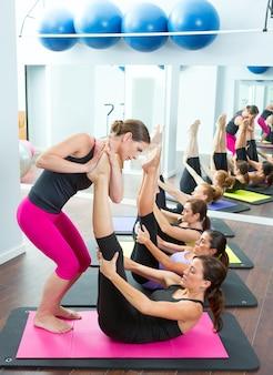 Aeróbic entrenador personal de pilates ayudando al grupo de mujeres.