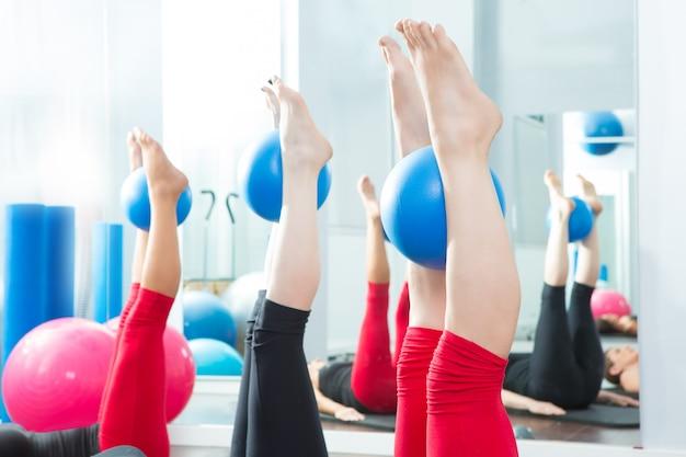 Aeróbicos de mujer con pies de pilates con bolas de yoga.