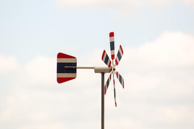 Aerogenerador de bandera tailandesa, color de cielo natural difuminado, el viento sopla a través, lo que hace que la hélice gire, espacio libre en la imagen