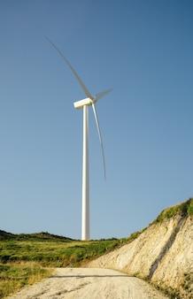Aerogenerador en la colina que genera electricidad sobre un fondo de cielo azul. concepto de producción de energía limpia y ecológica.