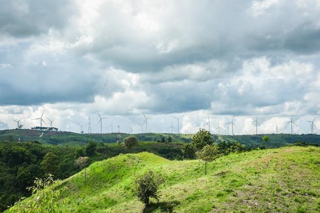 Aerogenerador de molino de energía renovable en paisaje de montaña con poste de alta tensión y poste eléctrico en colinas /