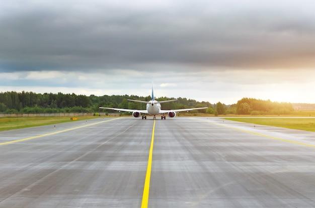 Aeronaves que gravan para despegar en pista en la pista en la distancia.