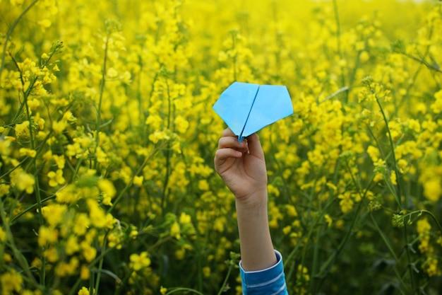 Aeroplano de papel en manos de los niños en fondo amarillo.