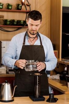 Aeropress café y guapo barista barbudo en café