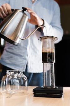Aeropress coffee close up alternativa making by barista in the cafe foto vertical