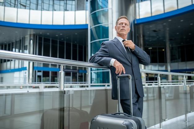 Aeropuerto, esperando. hombre adulto serio en traje oscuro y corbata con maleta de pie esperando el vuelo en el aeropuerto