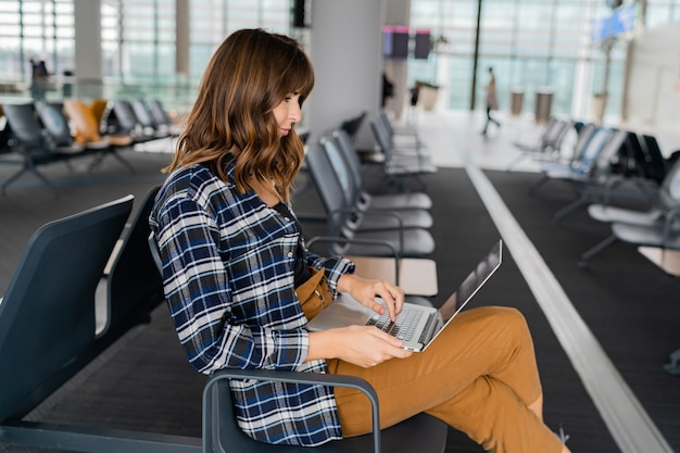 Aeropuerto joven pasajera con laptop sentada en el hall de la terminal mientras espera su vuelo