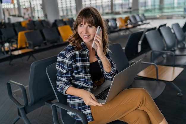 Aeropuerto joven pasajera con teléfono inteligente y computadora portátil sentada en el pasillo de la terminal mientras espera su vuelo