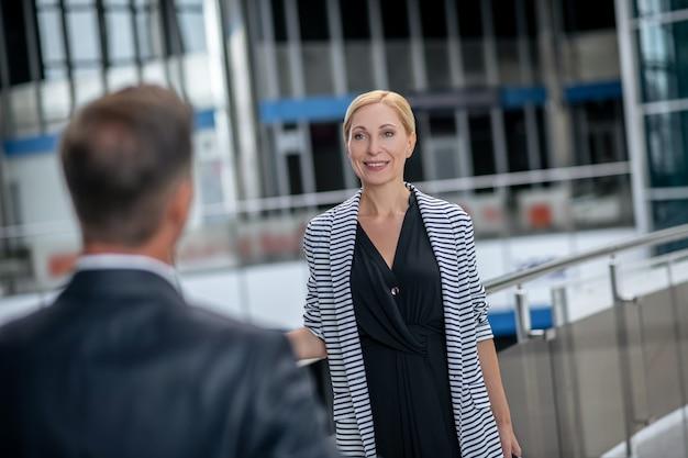 Aeropuerto, reunión. sonriente mujer de negocios rubia en vestido y chaqueta a rayas y espalda de hombre acogedor en traje formal oscuro