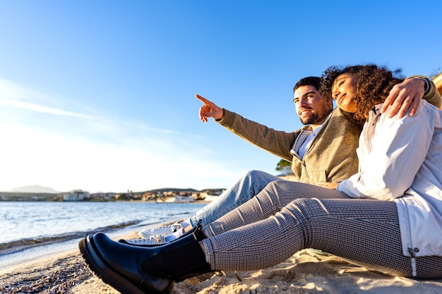 Afectuosa pareja de jóvenes enamorados sentados en la orilla del mar cerca del agua del océano uno al lado del otro mirando la puesta de sol. guapo abrazando novia apuntando al horizonte en viajes de vacaciones de invierno