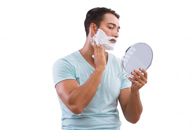 El afeitar del hombre aislado en el fondo blanco