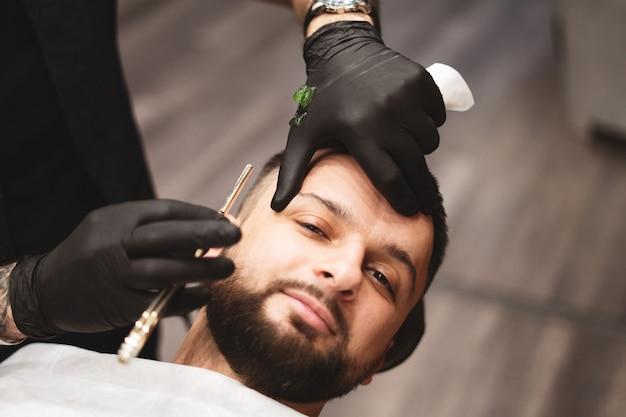 Afeitarse la barba en una barbería con una navaja de afeitar peligrosa. peluquería barba cuidado. secado, corte, corte de barba. enfoque selectivo.