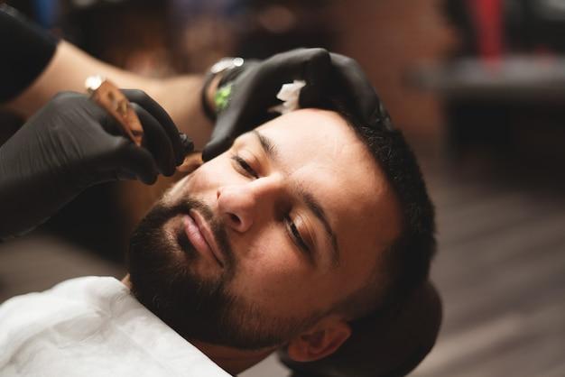 Afeitarse la barba en una barbería con una navaja de afeitar peligrosa.