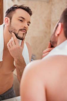 Afeitarse o no afeitarse. apuesto joven tocando su rostro y sonriendo mientras está de pie frente al espejo
