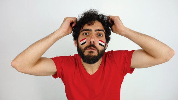 Aficionado al deporte con la bandera de egipto maquillaje en su rostro decepcionado con su equipo