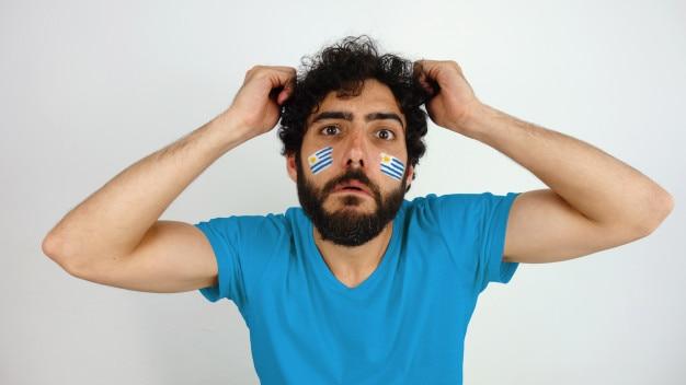 Aficionado al deporte con la bandera uruguay maquillaje en la cara decepcionado con su equipo