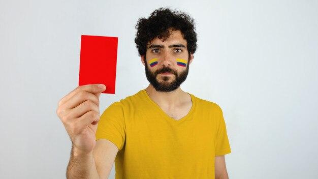 Aficionado al deporte con una tarjeta roja. hombre con la bandera de colombia maquillaje en la cara