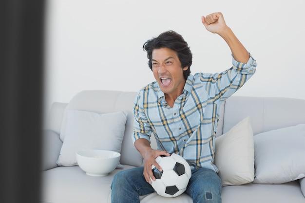 Aficionado al fútbol animando mientras ve la televisión