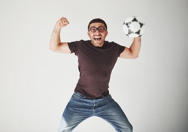 Aficionado al fútbol emocionado con un fútbol aislado en blanco.
