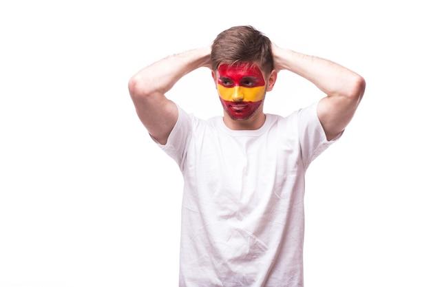 Aficionado al fútbol joven español con gesto triste aislado en la pared blanca